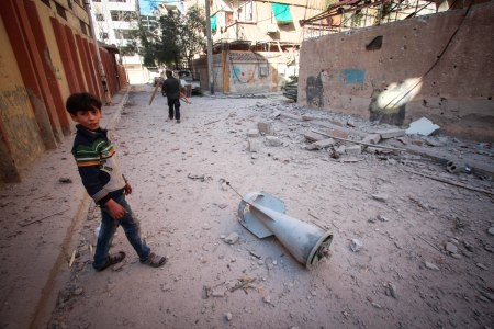 Douma, Syria. 20th Mar, 2018. A child stands next to one of the flying missiles that destroyed his house.General view of the aftermath of the air strikes on Douma city where at least 51 people were killed.The town of Douma in the outskirt of Damascus is o